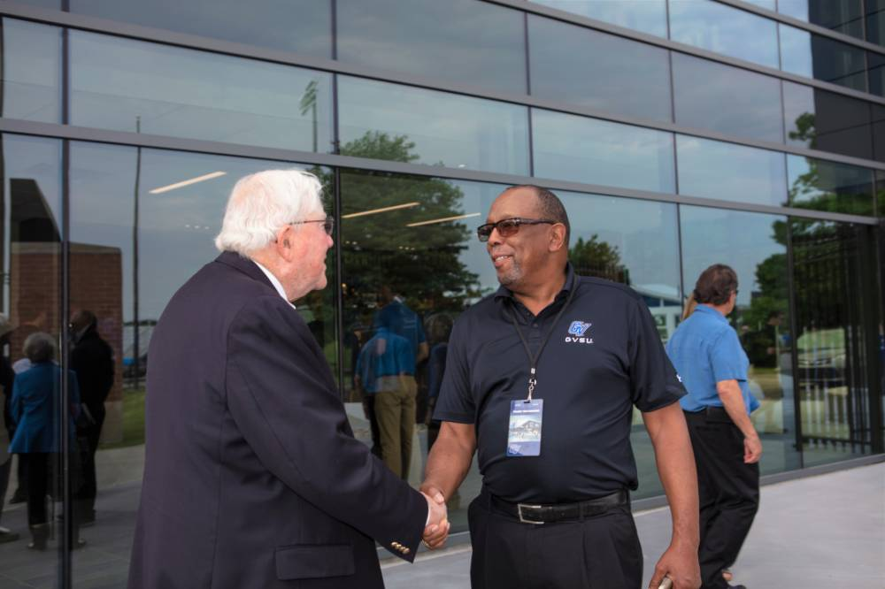 President Emeritus Don Lubbers shaking hands with a guest at the Jamie Hosford Football Center dedication.